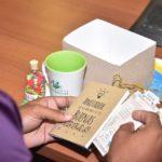 Persona recibe Tazas para Cafe Libretas Hechas a Mano en Caja