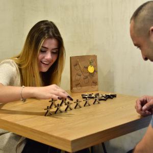 pareja jugando Jenga humana en la oficina